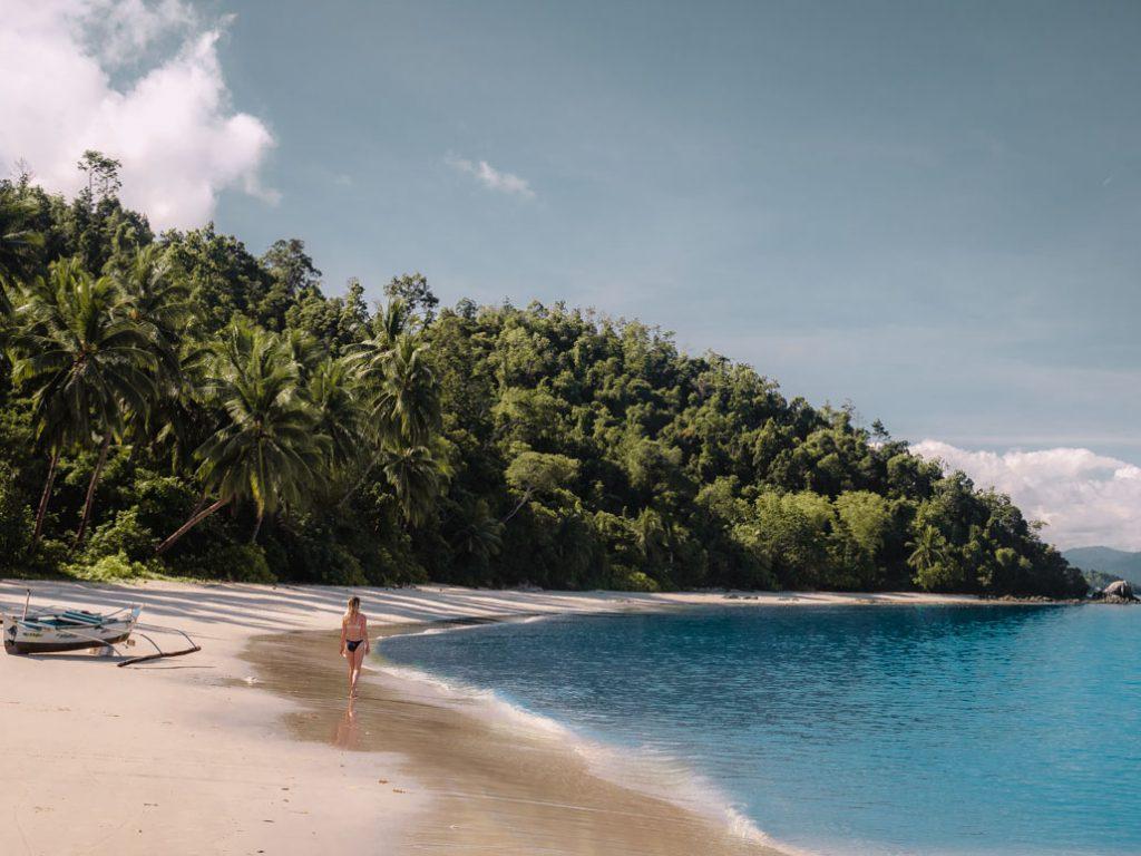 Girl walking along paradise beach at Palawan Camping in Port Barton