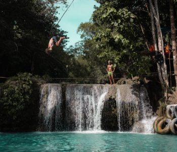 A man backflips on the rope swing at Cambugahay Falls, Siquijor, Philippines