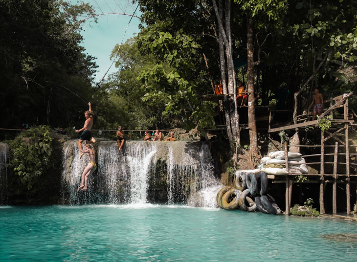 A couple rope swing at Cambugahay Falls, the girl lets go early. Siquijor, Philippines