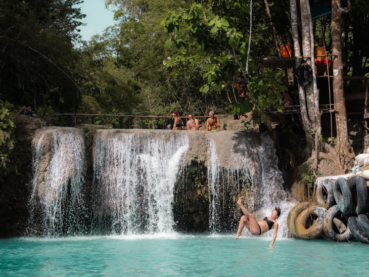 A girl falls from the rope swings at Cabugahay Falls, Siquijor, Philippines
