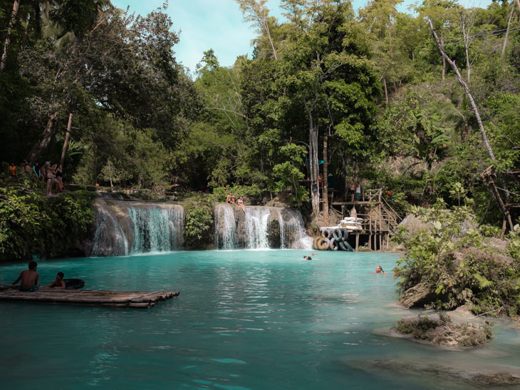 An open view of the turquoise waters of Cambugahay Falls, with some people in the water. Siquijor, Philippines