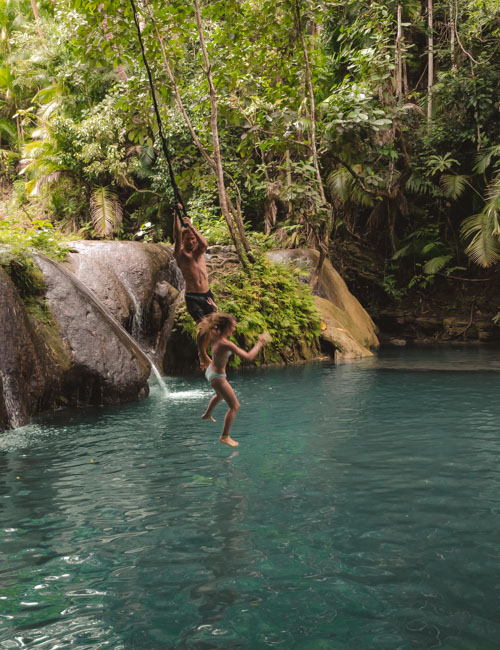 A couple fall from the rope swing at Laagan Falls, Siquijor, Philippines