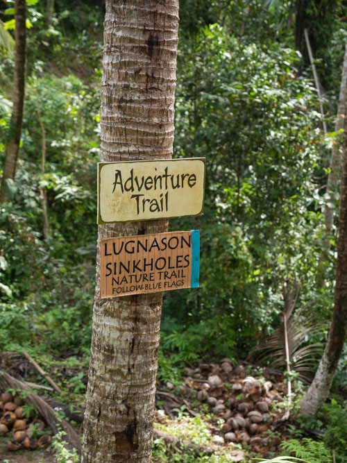 A sign shows 'adventure trail' and 'lugnason sinkholes' at Lugnason Falls, Philippines