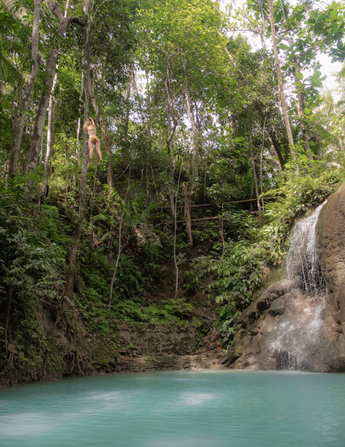 A girl rope swings on the 9m platform above turquoise waters at Lugnason Falls, Siquijor, Philippines