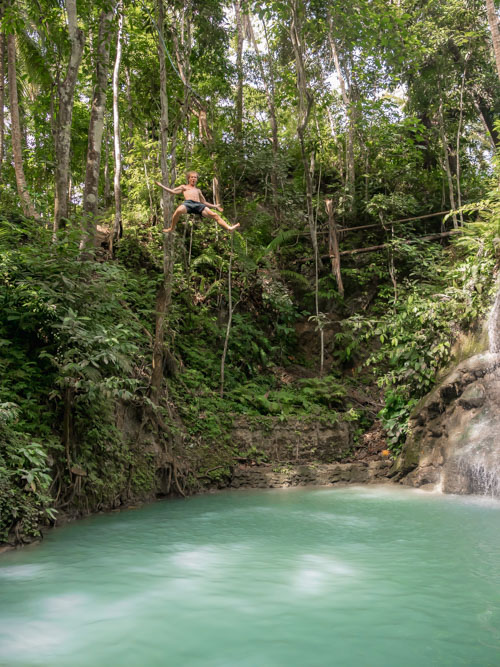 A man rope-swings from a 9m platform above turquoise waters at Lugnason Falls, Siquijor, Philippines