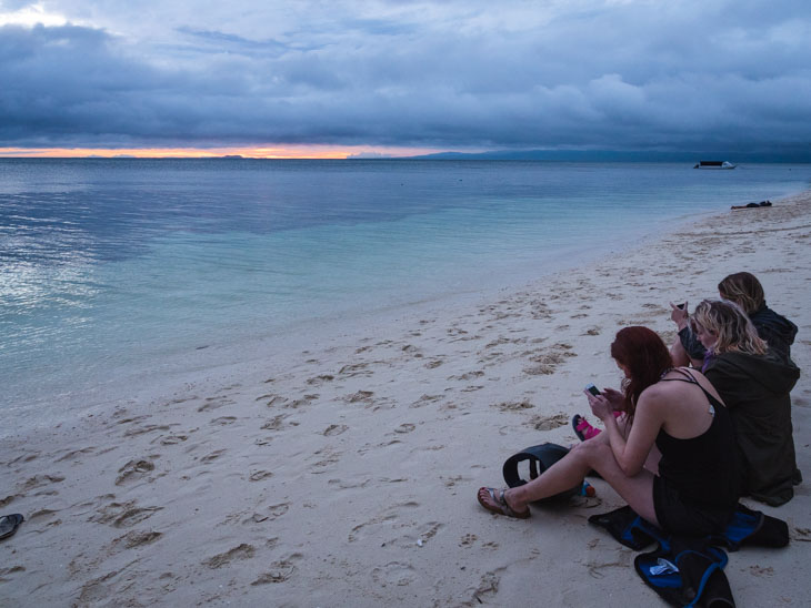 Girls sit on Paliton Beach, waiting for sunset. Siquijor, Philippines