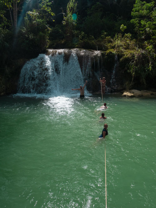 People playing about in water under waterfall in Bohol Philippines