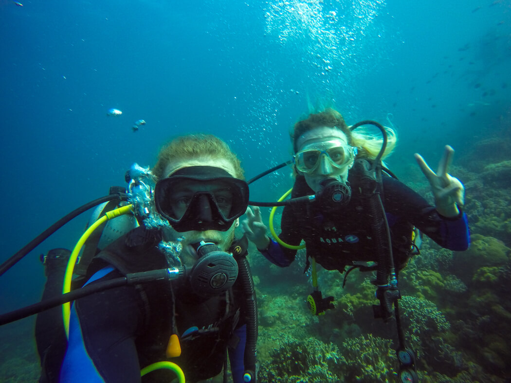 A couple take a selfie underwater at Apo Island, Philippines