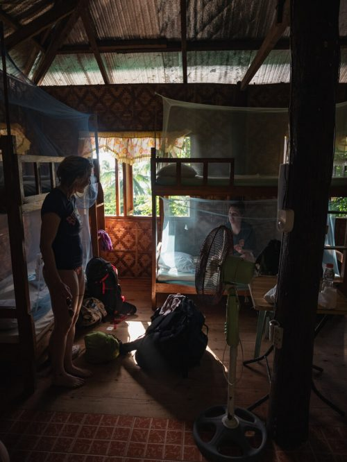 Two girls sit in a dormitory on Apo Island, Philippines