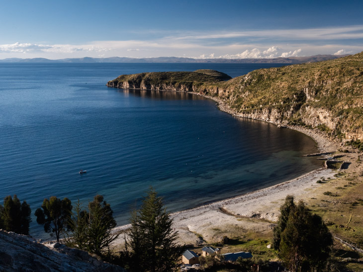 A landscape view of the width of the second beach at Challapampa with blue waters and sunshine, Isla del Sol, Bolivia