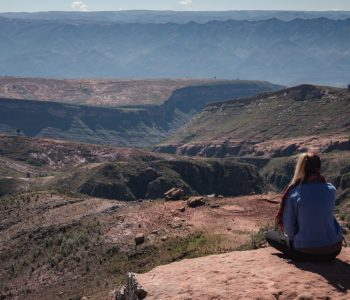 A girl sits on high rocks with great views at La Ciudad de Itas, Torotoro National Park, Bolivia