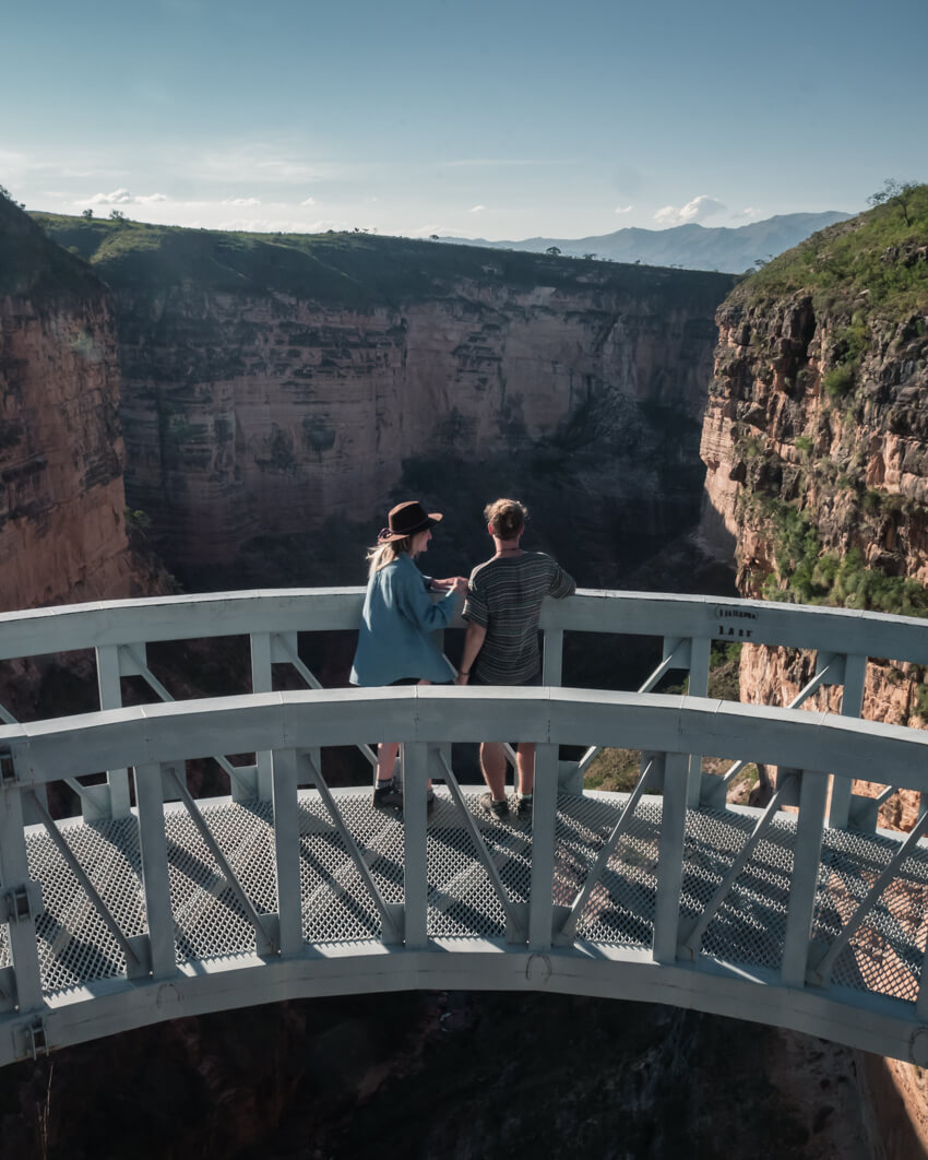 A couple stand on an open-air walkway at Torotoro Canyon, Bolivia