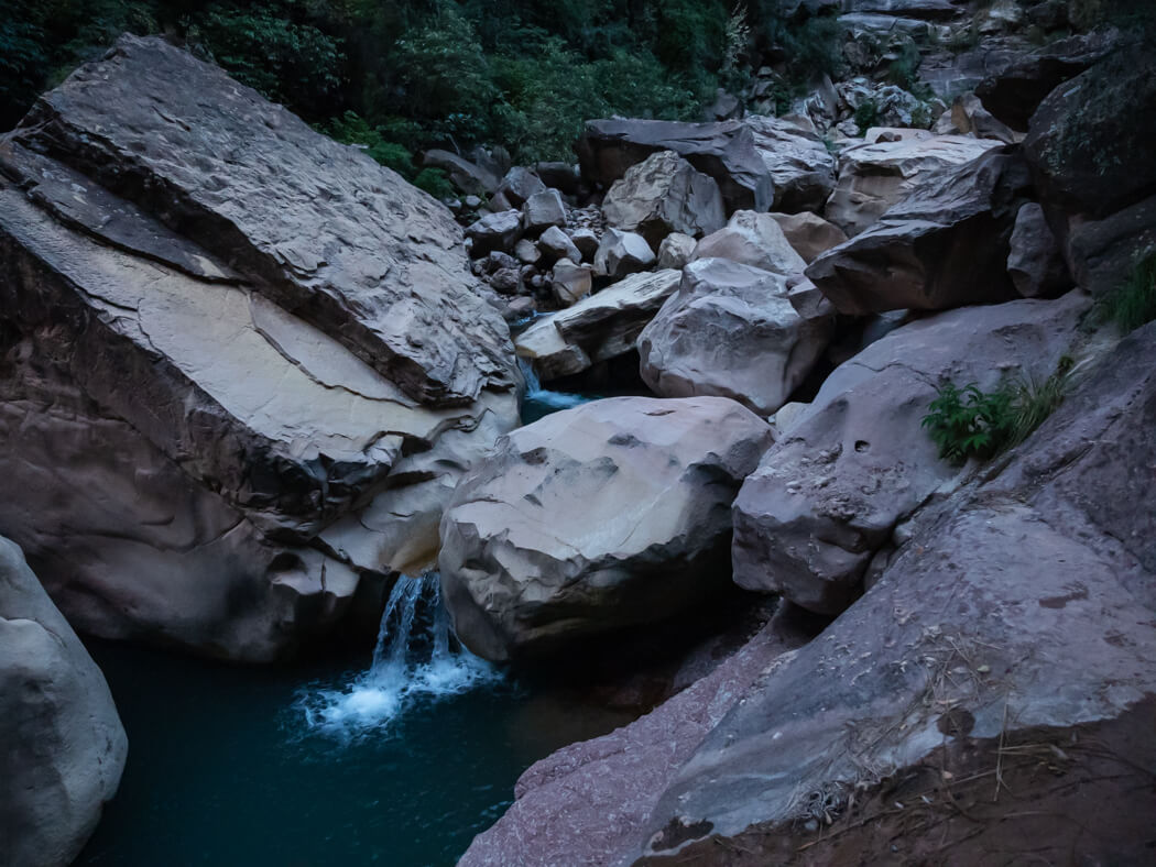 A stream leads in to a large pool among the rocks in El Vergel, Torotoro National Park, Bolivia