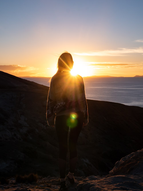 A girl in front of sunset on the north of Isla del Sol, Bolivia