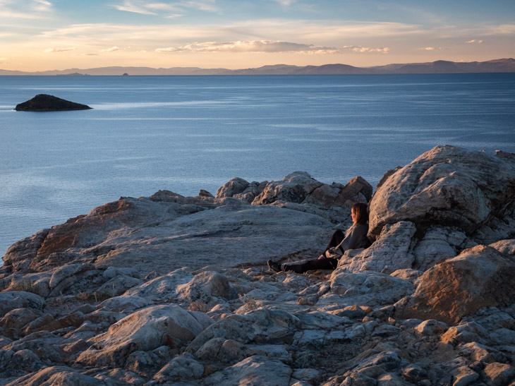 A girl sits on the rocks at sunset, north Isla del Sol, Bolivia