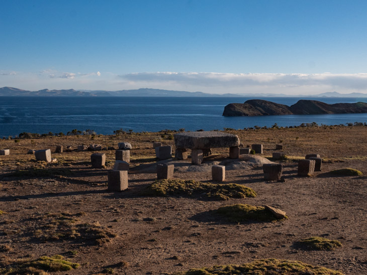Small rocks create the Incan ruins of the table of sacrifice with a lake backdrop, north Isla del Sol, Bolivia