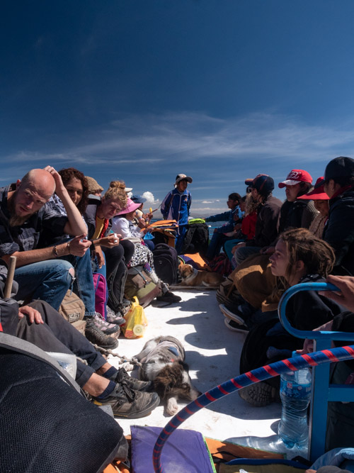 A crowded boat platform with dogs, tourists and locals, Bolivia