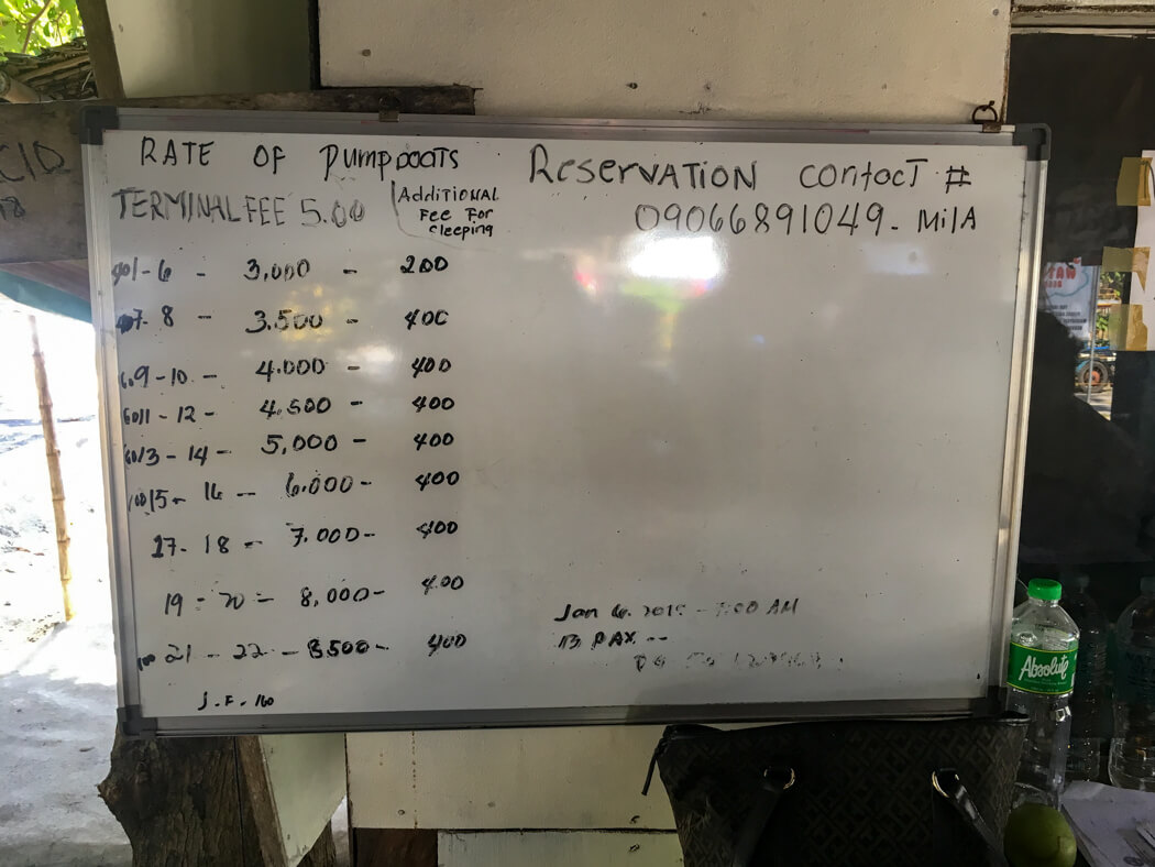 A whiteboard showing fees for the transfer from Malatapay to Apo Island, Philippines