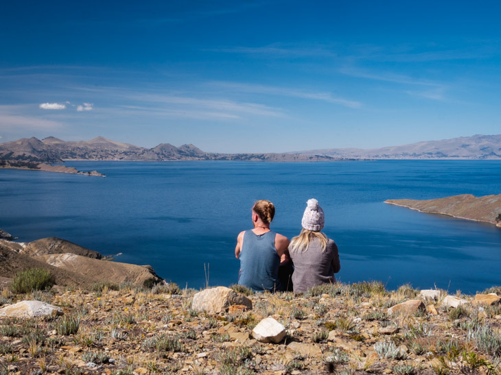 A couple sit with their back to the camera and a view of Lago Titicaca from Isla del Sol, Bolivia