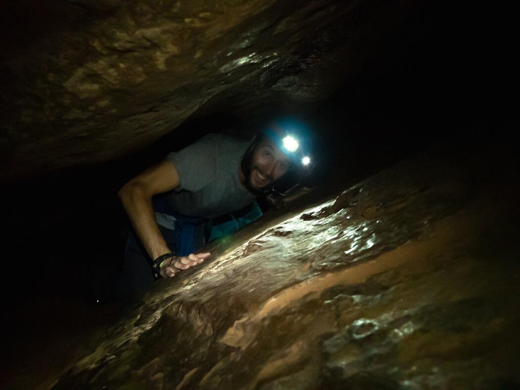 A tourist squeezes through a tight space in Caverna de Umajalanta, Torotoro National Park, Bolivia