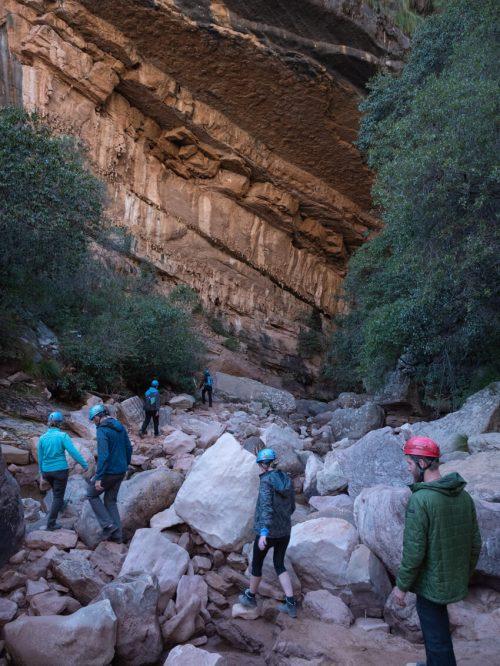People in helmets walking in to Cavernas de Umajalanta, Torotoro National Park, Bolivia
