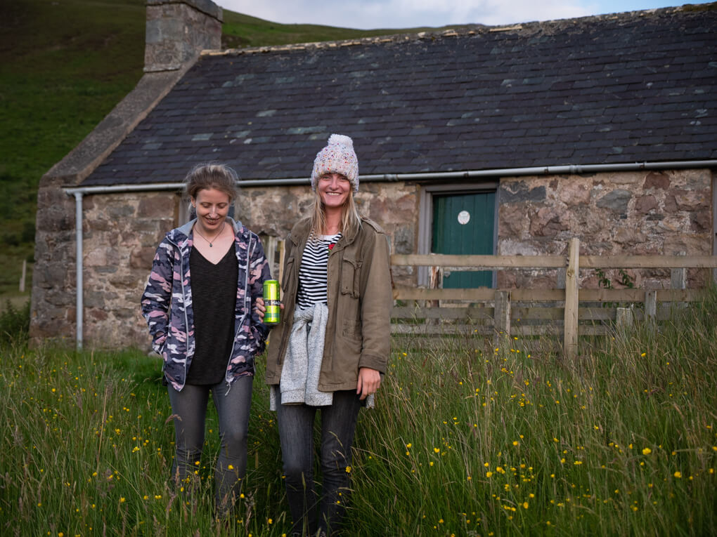Two girls stand outside Achnanclach Bothy near Tongue, Scotland