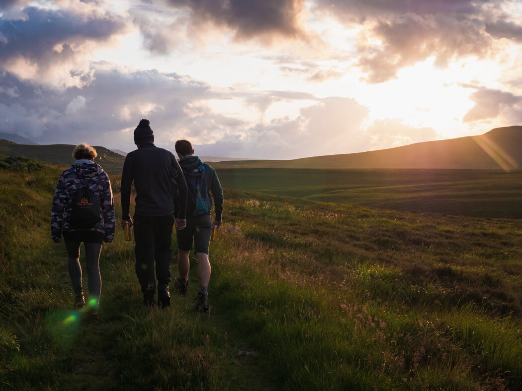 A group walk through long grass in sunset light near Tongue, Scotland