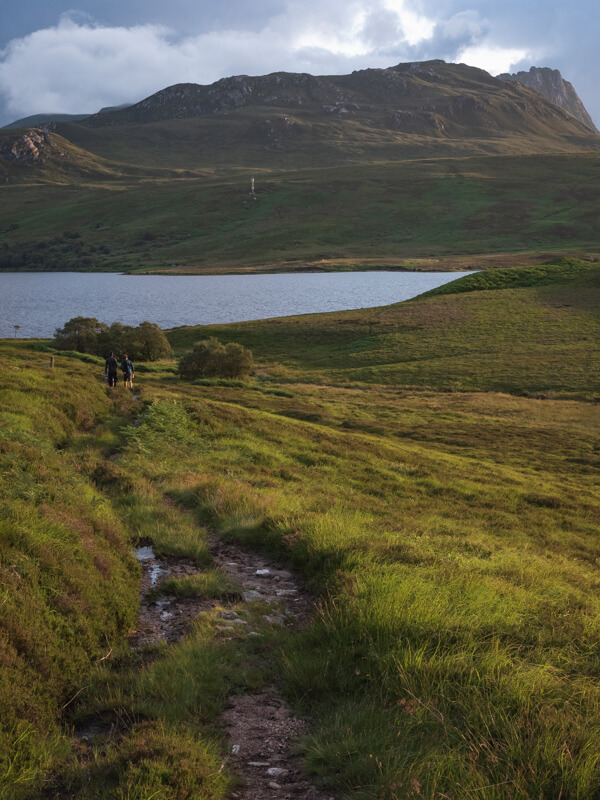 A group walking down to Loch Loyal with Ben Loyal in the distance