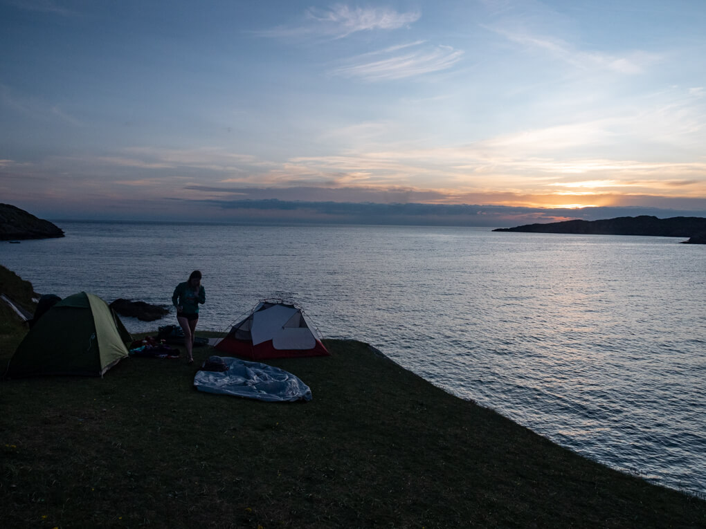 A girl between tents on the headland with sea in the background, near Lochinver