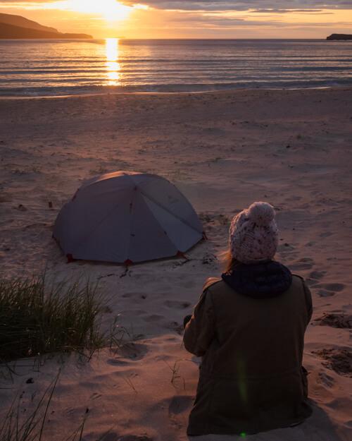 A girl watches the sun set behind a tent on Balnakeil Beach, Scotland