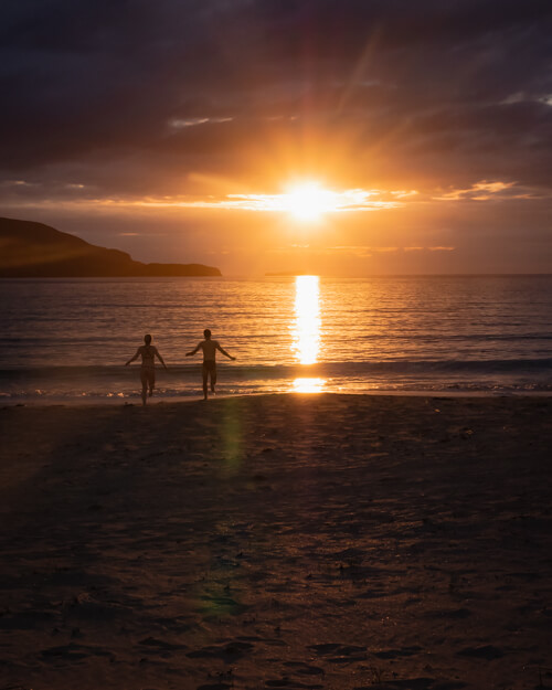 Two people run in to the sea for a swim at Balnakeil Beach during sunset