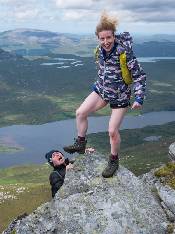 A girl pretends to kick her friend off a rock near Tongue, Scotland