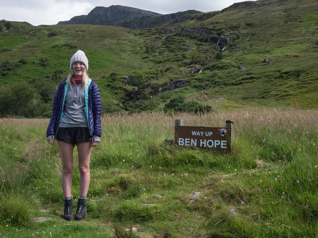 A girl stands next to a sign which reads 'way up Ben Hope' near Tongue, Scotland