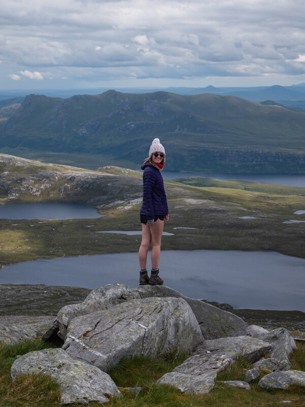 A girl stands at the peak of Ben Hope near Tongue, Scotland