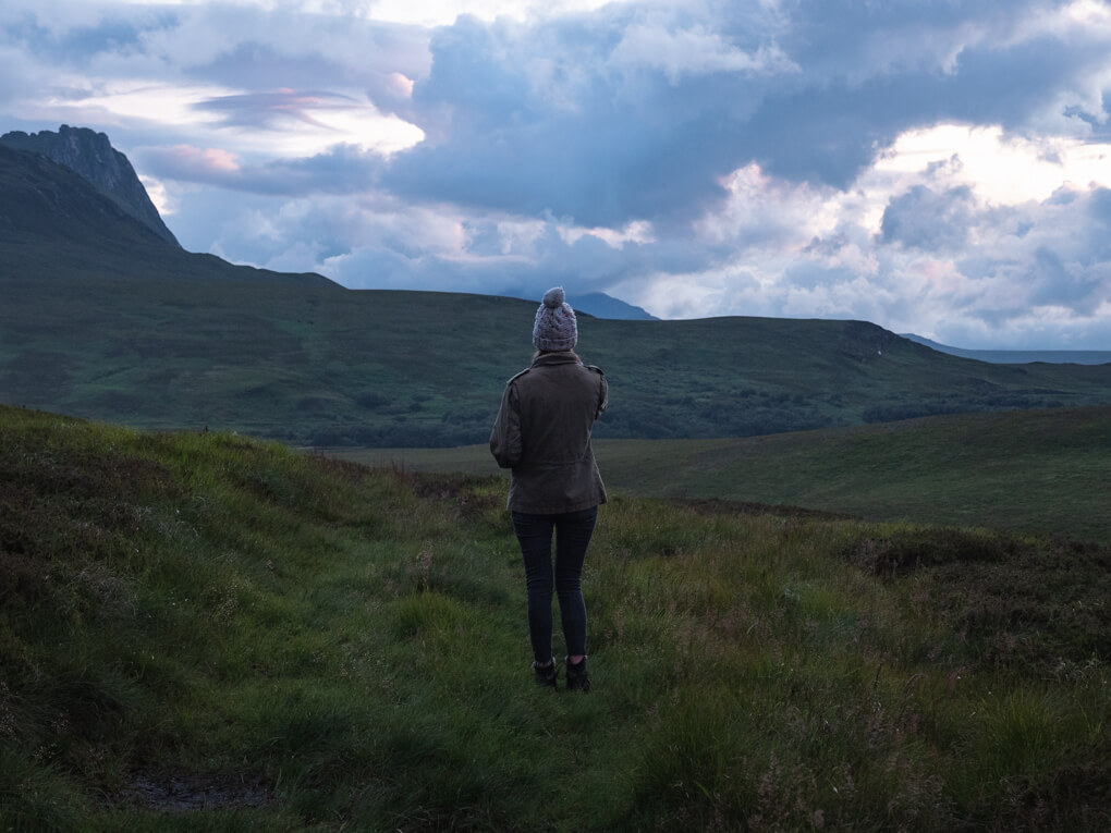 A girl stands with her back to the camera with Ben Loyal in the background, Tongue, Scotland