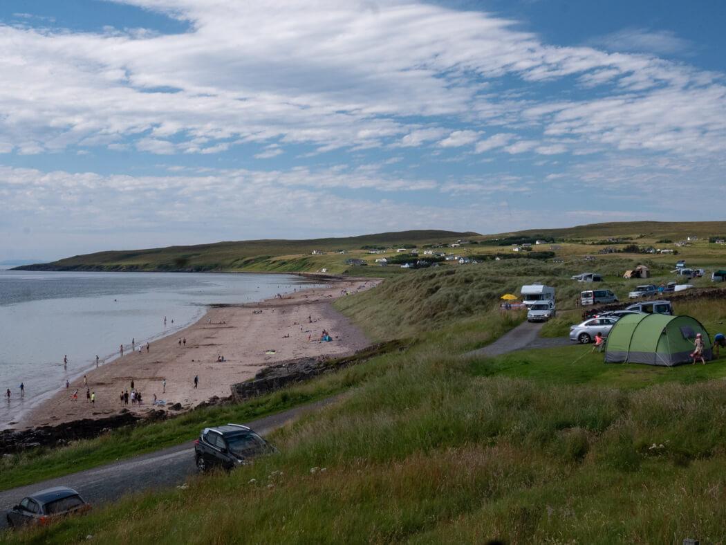 Tents, cars and campervans are parked at Big Sands resort, near Gairloch