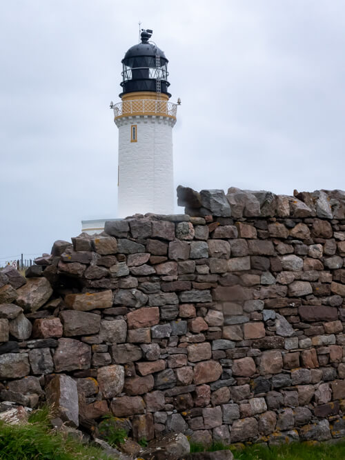 A white lighthouse against a stone wall at Cape Wrath, Scotland