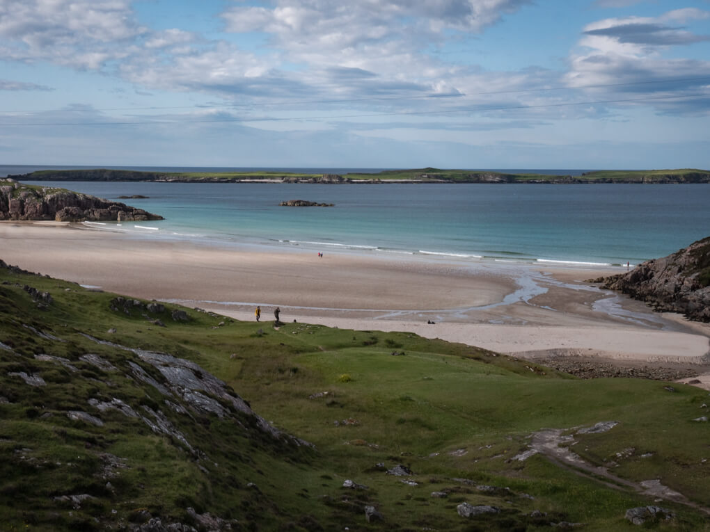 Grassy mounds, white sand and blue water of Ceannabeinne Beach from the car park, Scotland