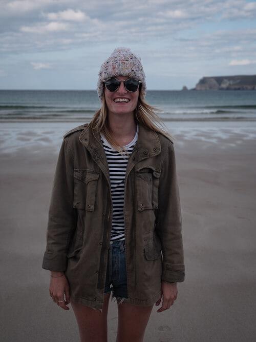 A girl smiles on the sand at Ceannabeinne Beach, Scotland