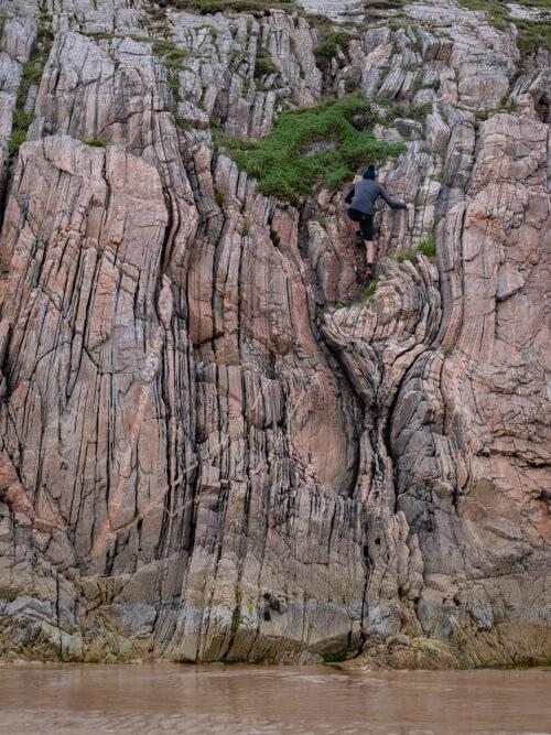 A man climbs a rock face on Ceannabeinne Beach, Scotland