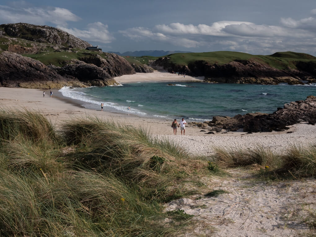 A couple walk on the white sands of Clachtoll Beach, Lochinver