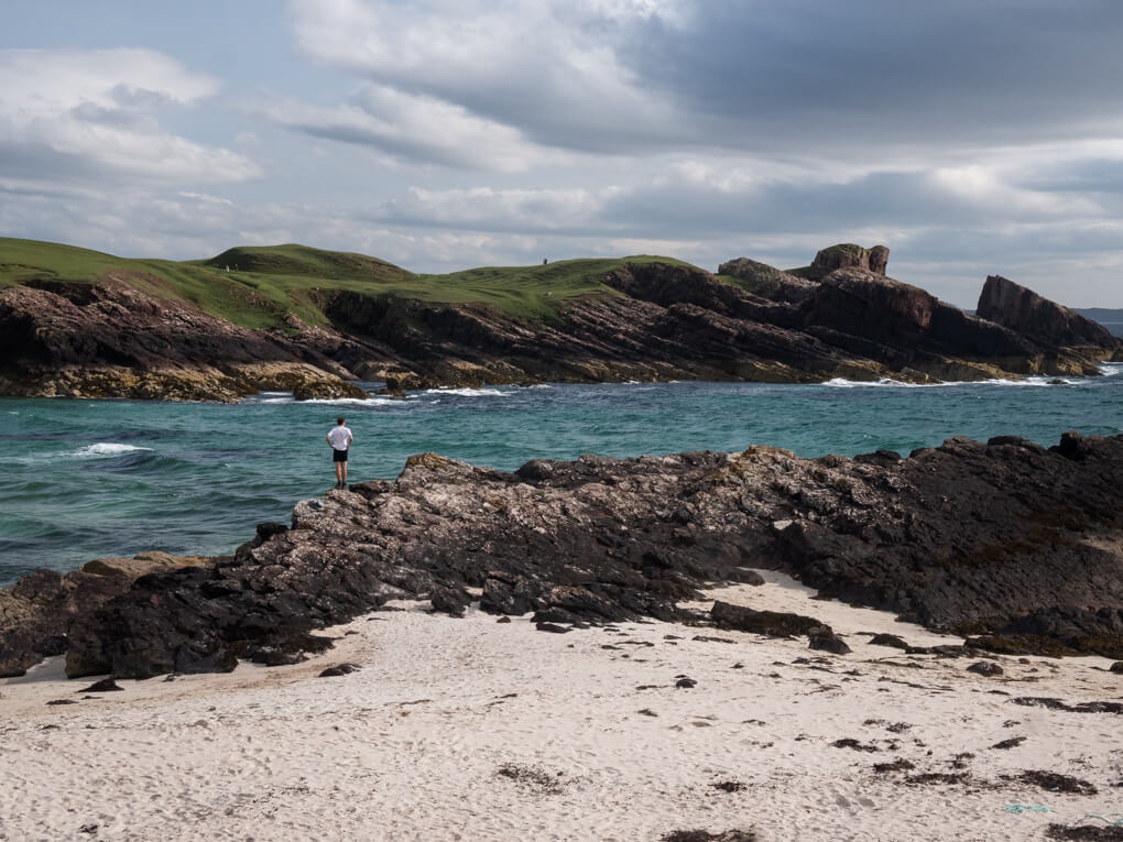 A man stands on the cove at Clachtoll Beach, Lochinver