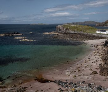 A white cottage on the beach with aqua water near Clashnessie