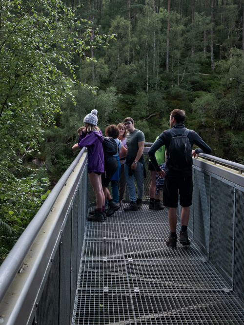 A group of people stand on the viewing platform at Corrieshalloch Gorge