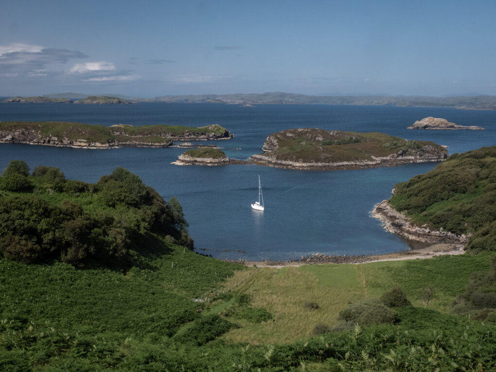 Blue waters at Drumbeg Viewpoint, with a yacht in the water