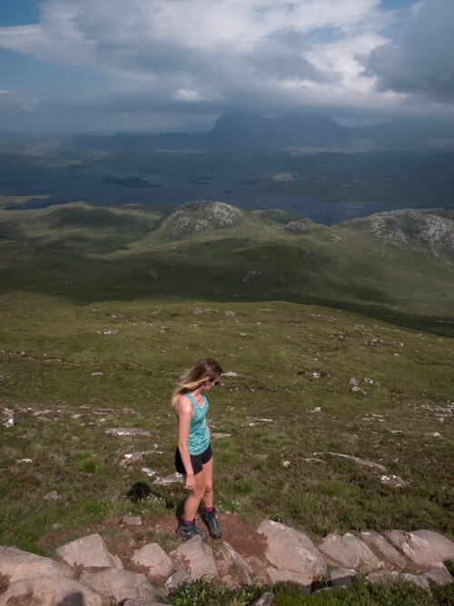 A girl stands on the heather at Stac Pollaidh with Assynt landscape in the distance