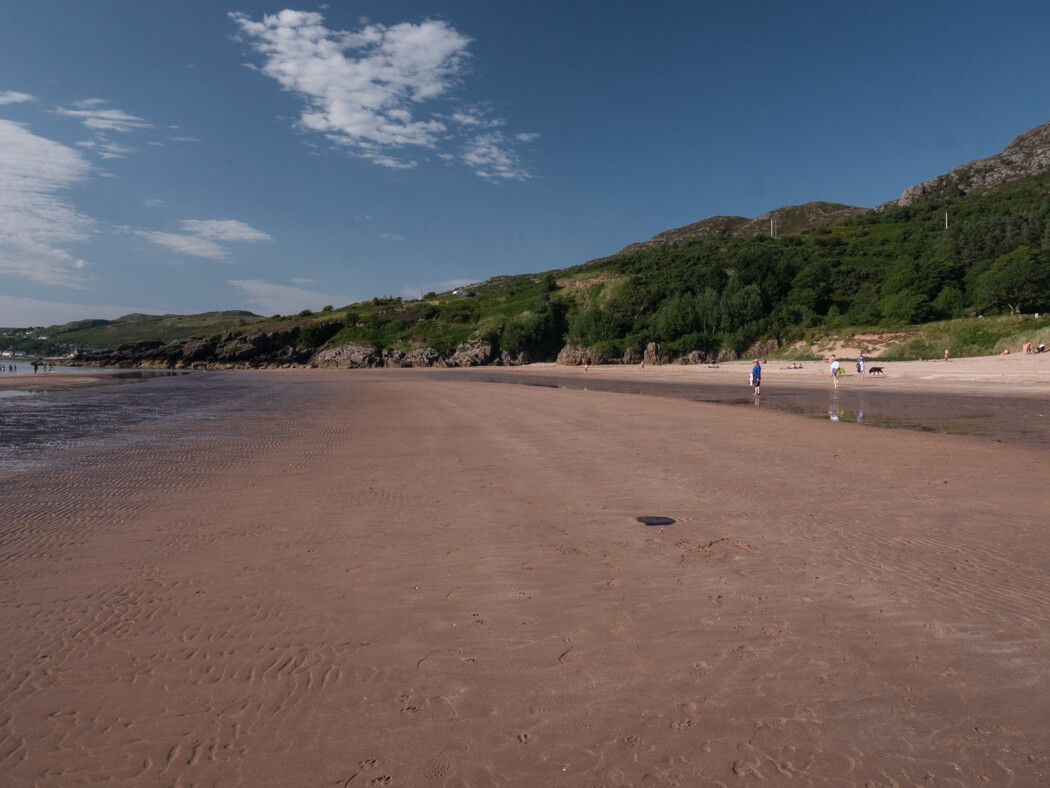 An empty beach in Gairloch with blue sky in the distance
