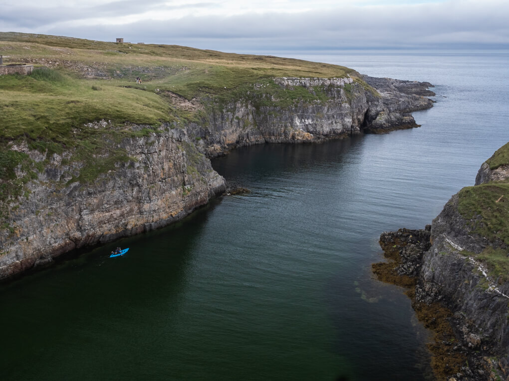 The rocky headlands which lead out of Smoo Cave with a kayak in the water, Durness