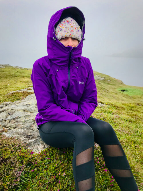 A girl sits in the rain with a rainjacket in Scotland