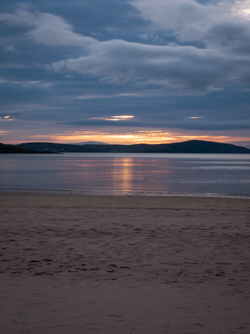 The sun sets over the water at Gruinard Beach